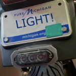 Image of Mini Auxiliary light bracket mounted on a motorcycle